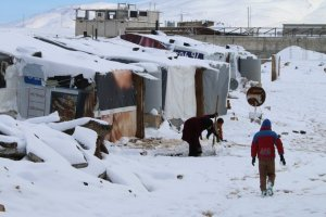 Syrian refugees walk in a makeshift camp covered in snow on February 20, 2015 on the outskirts of the Lebanese town of Baalbek. Blizzards dumped a blanket of snow over Israel, Jordan and Lebanon, with many residents urged to stay in their homes because of blocked or icy roads. AFP PHOTO / STR (Photo credit should read STR/AFP/Getty Images)