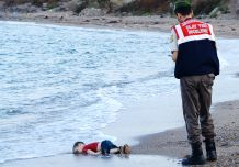 GRAPHIC CONTENT A Turkish police officer stands next to a migrant child's dead body off the shores in Bodrum, southern Turkey, on September 2, 2015 after a boat carrying refugees sank while reaching the Greek island of Kos. Thousands of refugees and migrants arrived in Athens on September 2, as Greek ministers held talks on the crisis, with Europe struggling to cope with the huge influx fleeing war and repression in the Middle East and Africa. AFP PHOTO / Nilufer Demir / DOGAN NEWS AGENCY = TURKEY OUT =